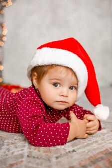 かわいい赤ちゃんサンタは贈り物を持ってクリスマスツリーの近くに家に座っています
