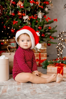 Cute baby santa sits at home near the christmas tree with gifts