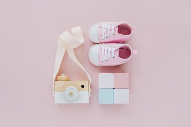나무 장난감 카메라와 다채로운 블록이 있는 귀여운 아기 신발. 파스텔 핑크 배경에 소녀를 위한 아기 물건과 액세서리 세트. 베이비 샤워 개념입니다. 패션 신생아입니다. 평평한 평지, 평면도