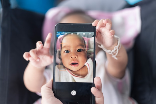 Cute baby shows his own photos on the smartphone on the stroller.