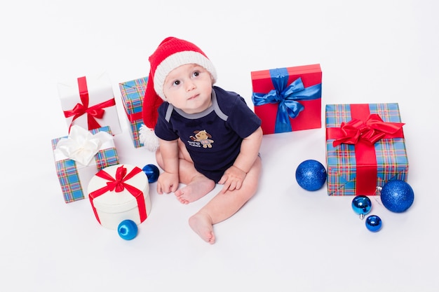 Cute baby sitting among christmas toys from boxes with gifts