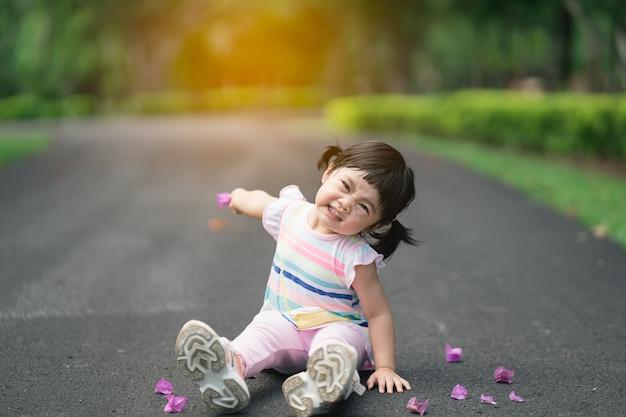 Милый ребенок сидит в саду, концепция деятельности на свежем воздухе милый ребенок