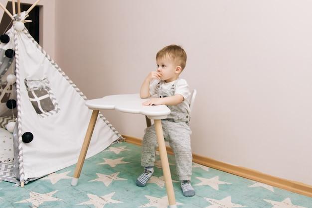 Милый ребенок сидит за столом и ест в питомнике белый, серый и синий. рядом с вигвамом и сумкой с игрушками