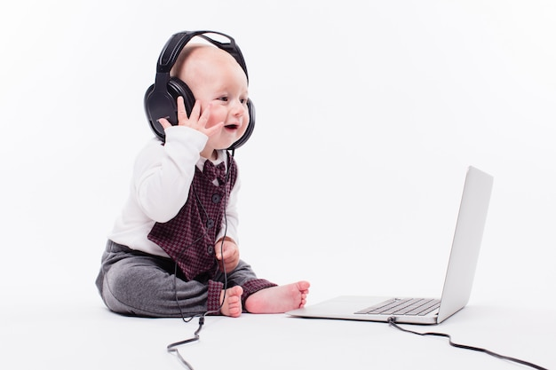 Cute baby sitting in front of a laptop wearing headphones on w