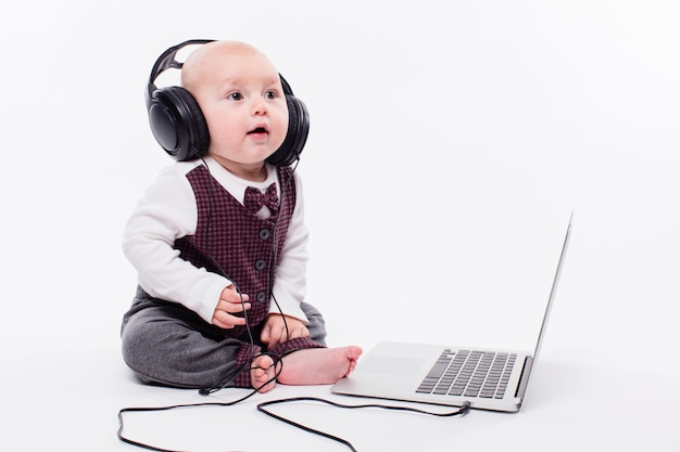 Cute baby sitting in front of a laptop wearing headphones