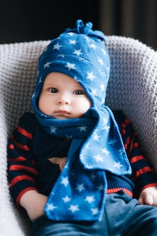 Cute baby sitting in a high chair in blue hat and scarf, swings