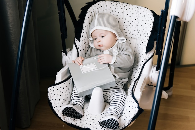 Cute baby sitting in a high chair, swings, holding a bag, copy space