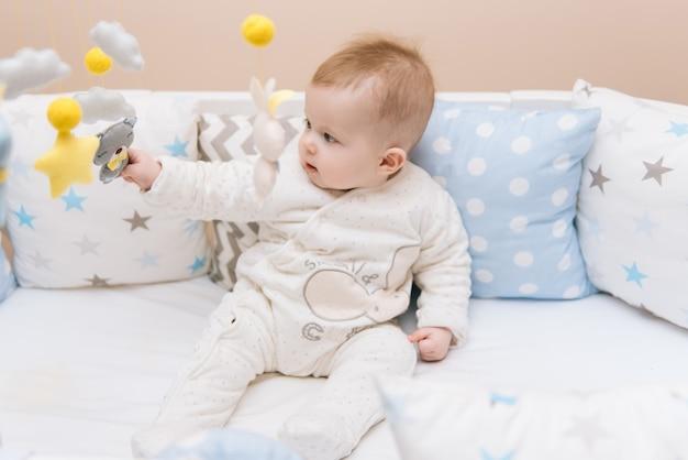 흰색 둥근 침대에 앉아 귀여운 아기. 어린 아이들을위한 가벼운 보육원. 유아용 장난감. 맑은 침실에서 느낌의 모바일 놀고 웃는 아이.