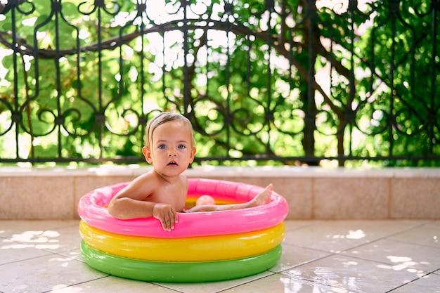 측면을 잡고 풍선 미니 수영장에 앉아 귀여운 아기