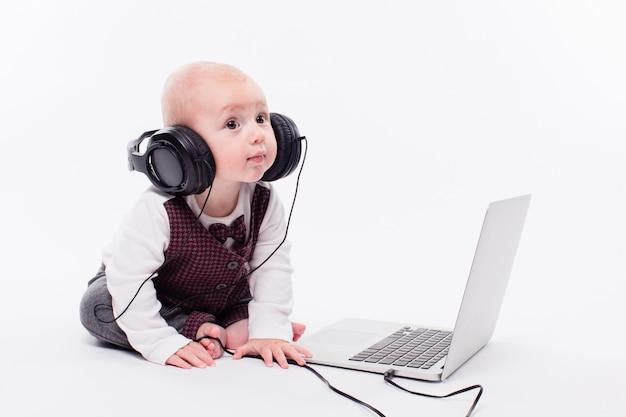 헤드폰을 쓰고 노트북 앞에 앉아 귀여운 아기