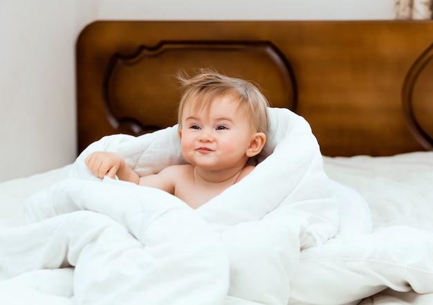 白い毛布に包まれたベッドに座っているかわいい赤ちゃん。赤ちゃんは11ヶ月です。