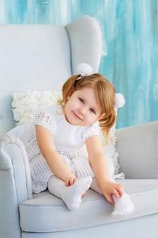 귀여운 아기 의자에 앉아입니다. 곱슬 금발 머리를 가진 행복 한 어린 소녀
