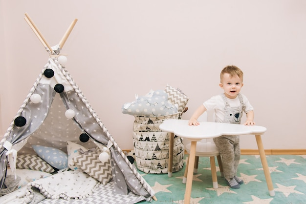 Cute baby sitting at the table in the children's room in white, gray and blue tones. near the teepee and a bag of toys