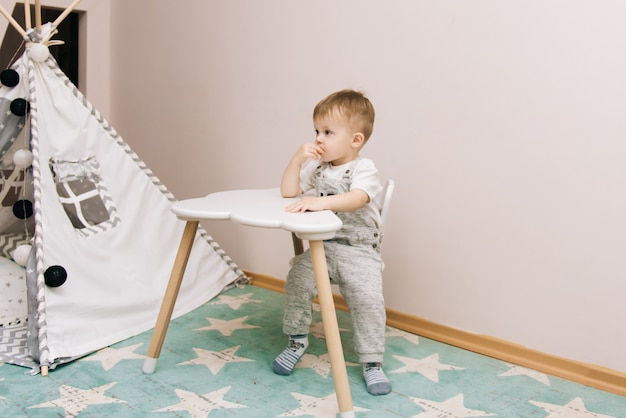 Cute baby sitting at the table and eating in the nursery white, gray and blue. near the teepee and a bag of toys
