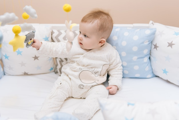 Cute baby sitting in a white round bed. light nursery for young children.  toys for infant cot. smiling child playing with mobile of felt in sunny bedroom.