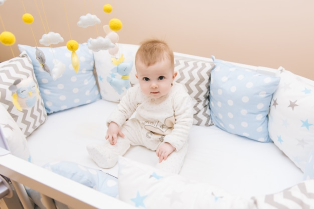 Cute baby sitting in a white round bed. light nursery for young children.