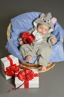 贈り物と衣装でマウスで眠っているかわいい赤ちゃん