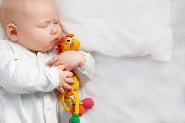 Cute baby sleeping with a toy on a white pillow.