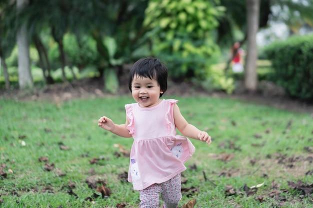 笑顔で公園で走っているかわいい赤ちゃん
