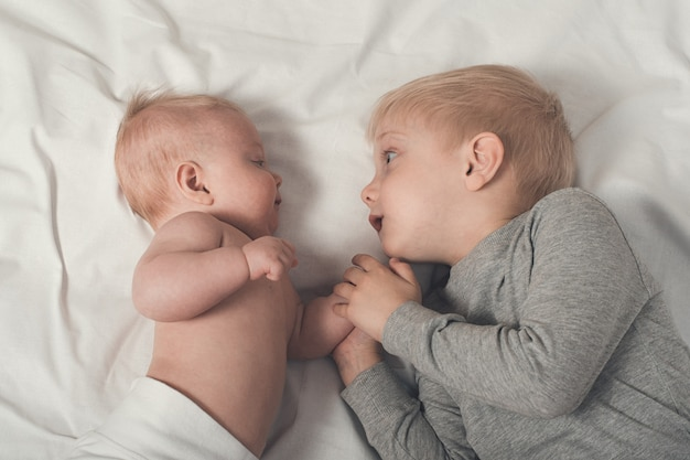 Cute baby and smiling older brother are lying on the bed. play and interact. top view