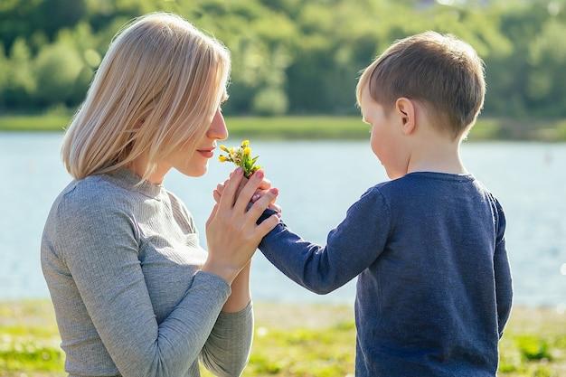 귀여운 아기 아들은 푸른 잔디를 배경으로 공원에 있는 아름다운 금발 어머니에게 꽃을 선물합니다. 어머니의 날 개념입니다.