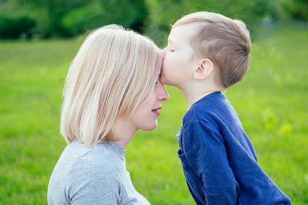 귀여운 아기(아들)는 푸른 잔디와 나무를 배경으로 공원에 있는 이마에 있는 어머니의 이마에 키스한다
