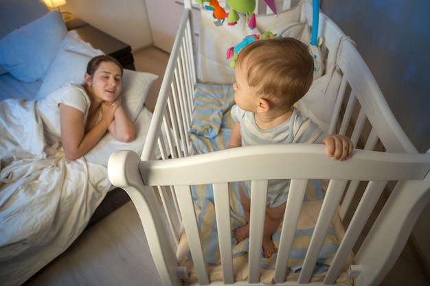 Cute baby standing in crib and looking at tired mother that fell asleep