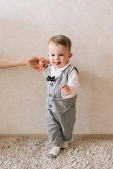 Милый малыш стоит, держа за руку свою маму, делая свои первые шаги, счастливое детство