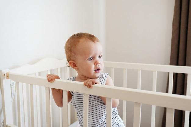 白い丸いベッドに立っているかわいい赤ちゃん。子供のための白い保育園。彼のベビーベッドに立つことを学ぶ少女。