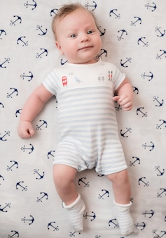 Cute baby in a striped suit lies. marine theme