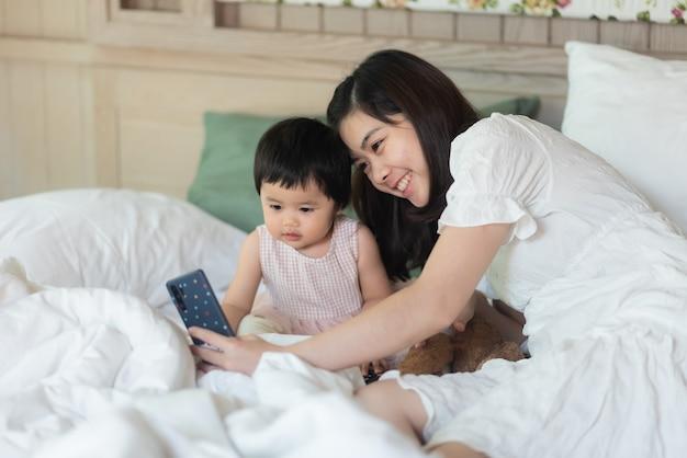 かわいい赤ちゃんは母親と一緒に写真を撮り、ベッドに座っています