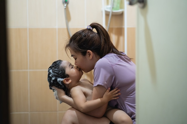 かわいい赤ちゃんはトイレで母親と一緒にシャワーを浴びる