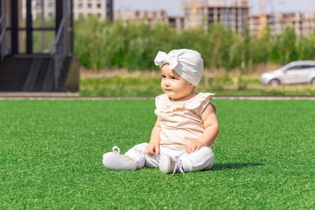 街の通りの背景に緑の芝生の上に座っているかわいい赤ちゃん幼児
