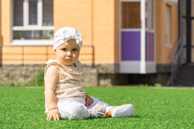 家の背景に緑の芝生の上に座っているかわいい赤ちゃんの幼児