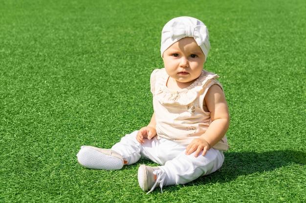 緑の芝生の上に座っているかわいい赤ちゃんの幼児