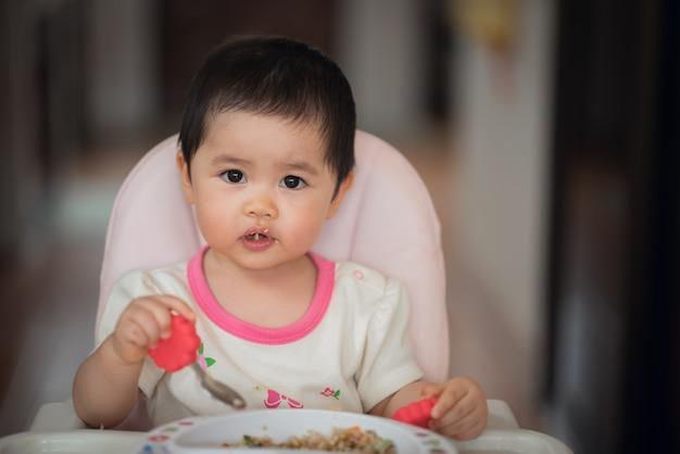 귀여운 아기가 자기 자리에서 혼자서 식사하려고합니다.