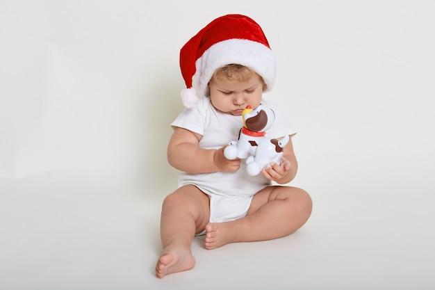 クリスマスの帽子と白いボディースーツを着て、床に裸足で座っている間、プラスチックのおもちゃの犬と遊ぶかわいい赤ちゃん