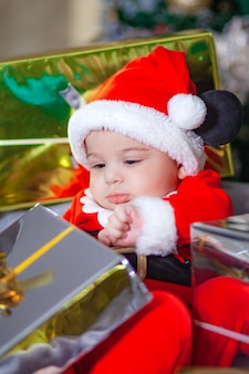 Cute baby wearing santa suit holding christmas gift, new year