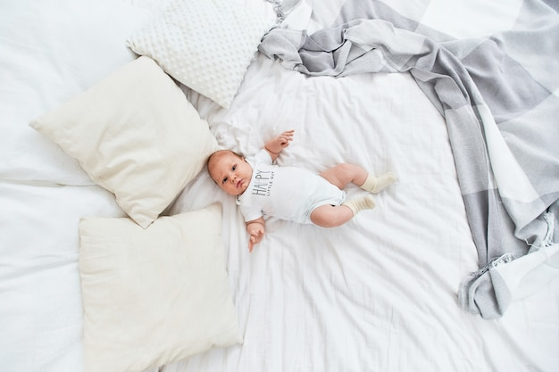 Cute baby in white bodysuit and socks, lying on his back on bed.