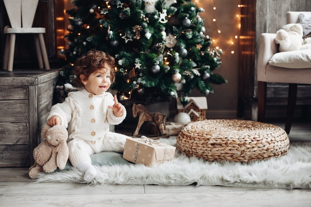 Cute baby in white with finger up sitting under christmas tree with teddy rabbit.