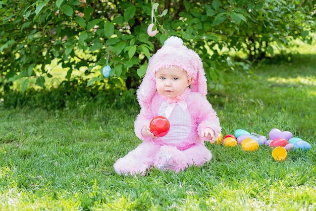 Cute baby with bunny costume and easter eggs