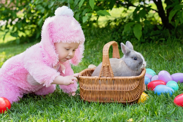 Cute baby with bunny costume playing with real rabbit