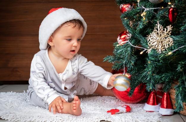 クリスマスツリーとかわいい赤ちゃん。クリスマスツリーの近くに座って、興味を持ってクリスマスの飾りに手を伸ばす幸せな子供