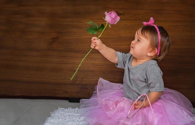 花とかわいい赤ちゃん。ピンクのドレスを着た床の子供、女の子はピンクのバラを見ます