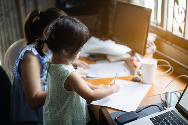 Cute baby working with her mother on working table