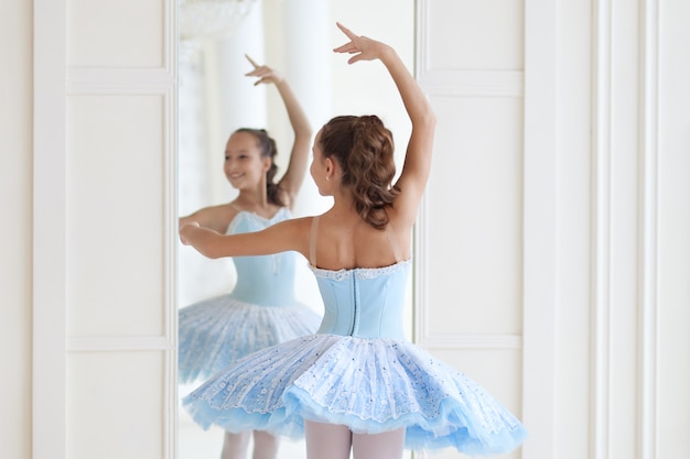 A cute ballerina in ballet costume and in pointe dances near the mirror. girl in the dance class. the girl is studying ballet. ballerina is dancing. the dancer is training at the mirror.