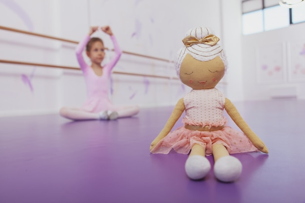 Cute ballerina doll on the foreground, little girl practicing ballet on the back, copy space. selective focus on a ballerina doll, girl exercising at ballet school on background