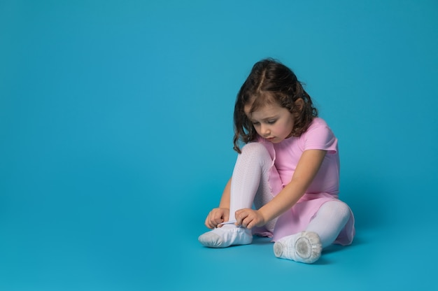 Cute ballerina focused on tying shoelaces on ballet shoes sitting