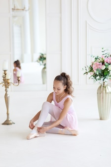 A cute  ballerina in a pink ballet costume is sitting on the floor and tying pointe shoes. ballerina in the dance class.the girl is studying ballet.