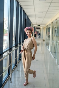 Cute barefoot woman in brown clothes posing inside big business center